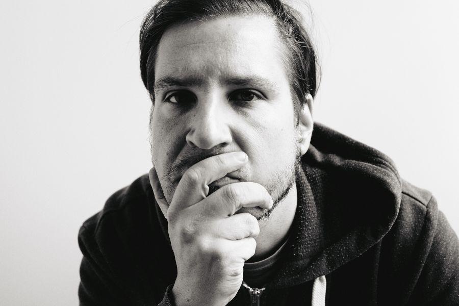 die deutSCHule; Lehrer Porträt Diego schaut nachdenklich auf die Hand gestützt in die Kamera