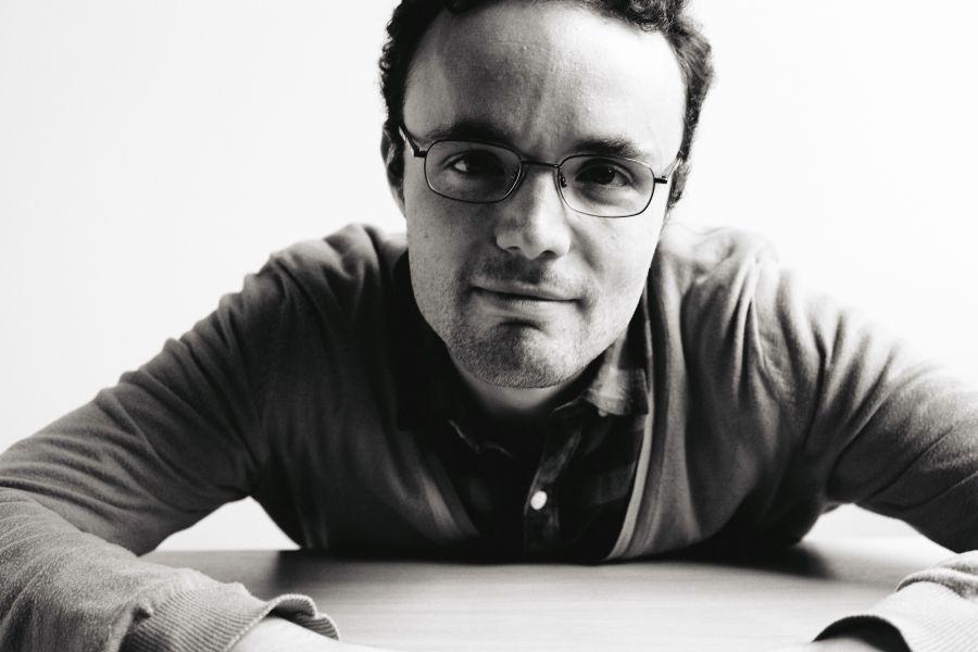 die deutSCHule; Lehrer Porträt Lorenzo schaut auf einen Tisch gestützt in die Kamera