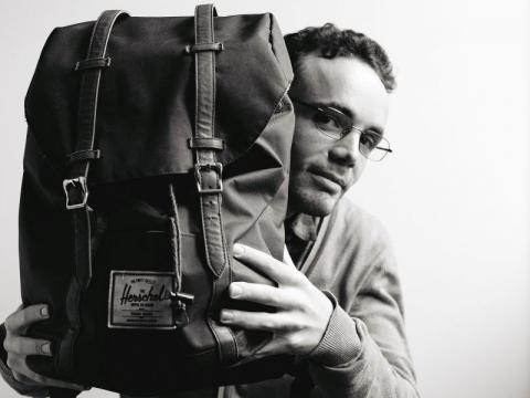 die deutSCHule; Lehrer Porträt Lorenzo präsentiert seinen Reiserucksack