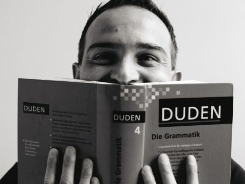 die deutSCHule; Lehrer Porträt Marco versteckt sich hinter einem Grammatik-Buch