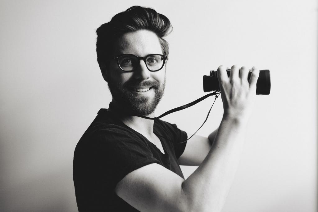 die deutSCHule; Lehrer Porträt Tillmann hält ein Fernglas vor sich und lächelt in die Kamera