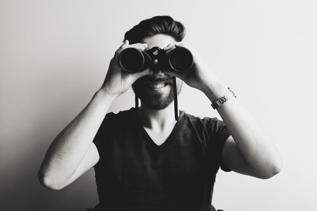 die deutSCHule; Lehrer Porträt Tillmann schaut durch ein Fernglas in die Kamera