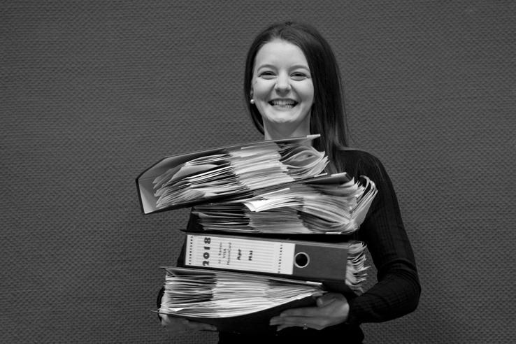 Team - die deutSCHule; Büroleiterin Tini Kall trägt lächelnd einen Stapel mit Akten auf den Armen
