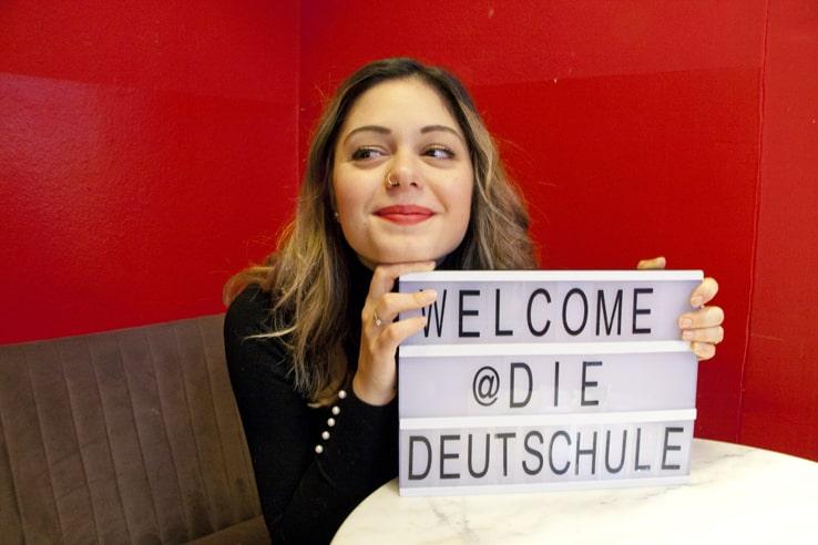 """die deutSCHule; Büromitarbeiterin hält ein Schild mit der Aufschrift """"welcome @ die deutSCHule"""""""