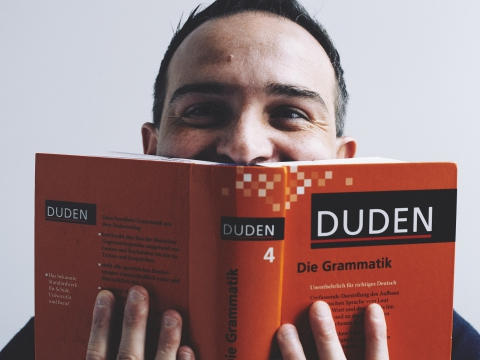 grammar course Berlin; teacher Marco holding a grammar book infront of his face